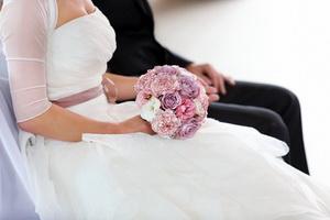 Brautpaar mit Rosenstrauß bei der Hochzeitszeremonie in der Kirche